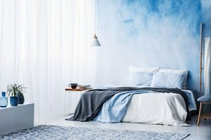 beautyful bedroom with a king bed and blue walls