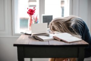 sleep deprivation effects, lady sleeping at daylight on desk