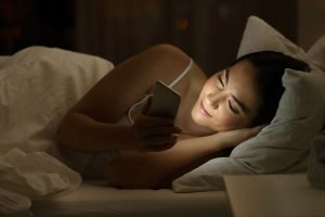 skiny girl not sleeping, playing with mobile phone