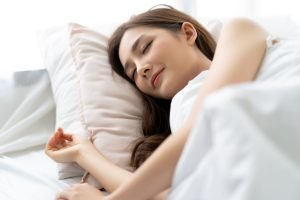 calm young pretty Asian woman sleeping in her bed and relaxing in the morning. Lady enjoying sweet dreams.