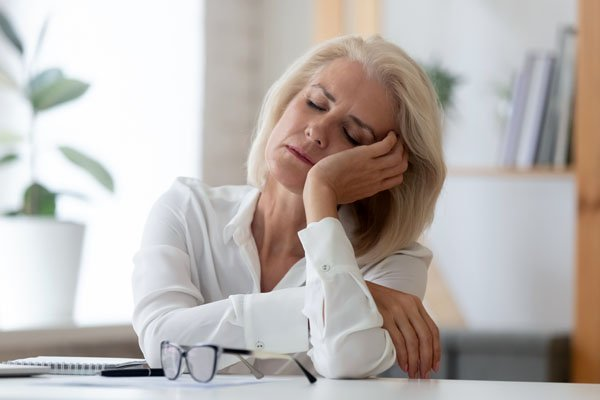 Exhausted menopause aged woman worker sit at office desk fall asleep distracted from work, tired senior businesswoman feel fatigue sleeping at workplace.