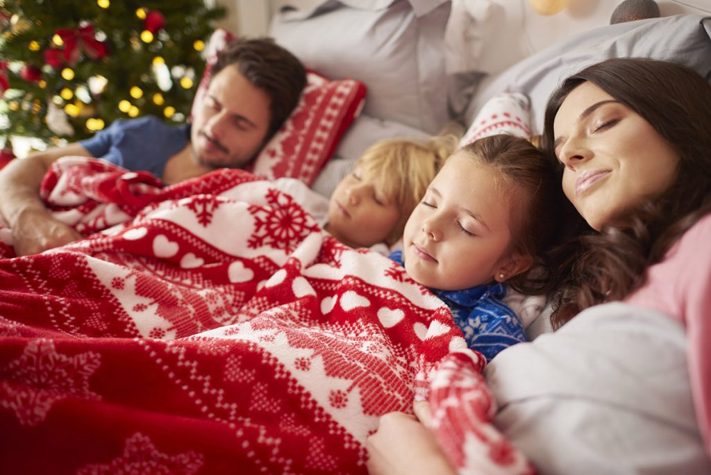 Family sleeping in a Christmas throw