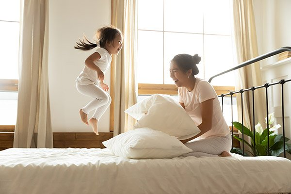 happy girl with mom on mattress