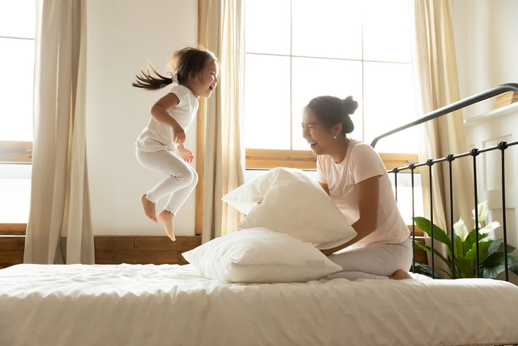 girl with mom jumping on mattress